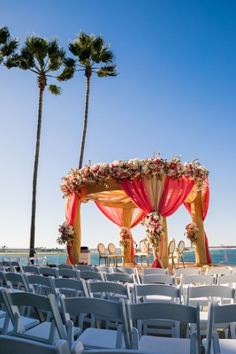 wedding ceremony facing ocean indian wedding mandap gold red drapery white pink flowers