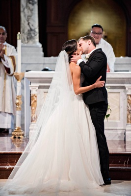 catholic wedding ceremony, bride and groom kiss, bride in reem acra ball gown