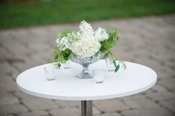 Wedding cocktail hour table with white hydrangeas, roses, greenery in mercury glass vase, candles