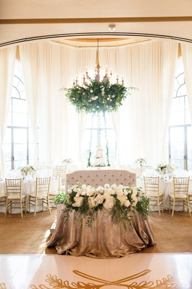 tufted love seat for sweetheart table with metallic linens and arrangement of white flowers, foliage