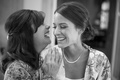 Black and white photo of bride and her mother laugh before getting ready for wedding ceremony