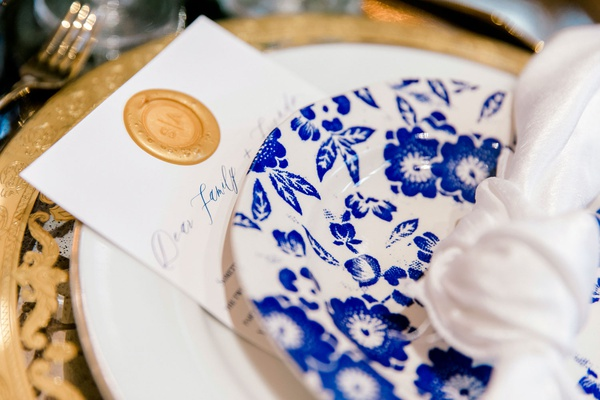 wax seal on on note to guests under blue and white plate gold charger plate