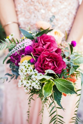 Red, white, yellow, fuchsia flowers with greenery in a bridesmaid bouquet with a rustic feel