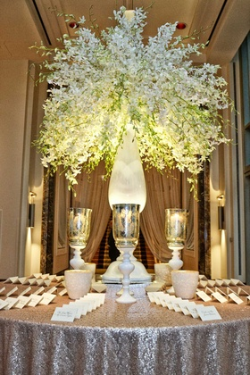 escort card table with silver metallic linen table candles and tall white green floral arrangement