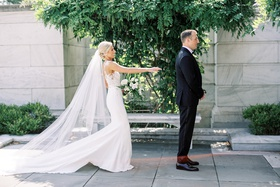 bride in form fitting pronovias wedding dress cathedral veil first look with groom tuxedo