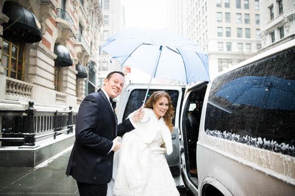 Groom holding umbrella for bride as they enter snowy wedding car