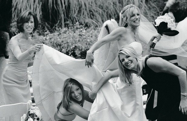 Black and white photo of bride being helped by attendants