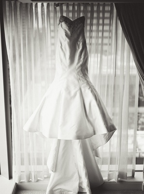 black and white photo of trumpet wedding dress with large open skirt and long train