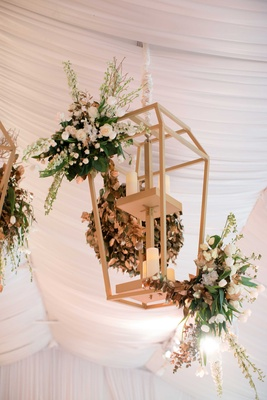 Gold lantern with pillar candle at wedding reception tent with greenery flowers over dance floor