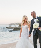 a newlywed couple in a wedding dress and blue tuxedo walks on beach mexico