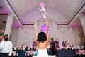 Bride tossing pink rose bouquet to friends