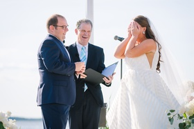 bride in striped hayley paige wedding dress covers face during ceremony, groom in navy suit