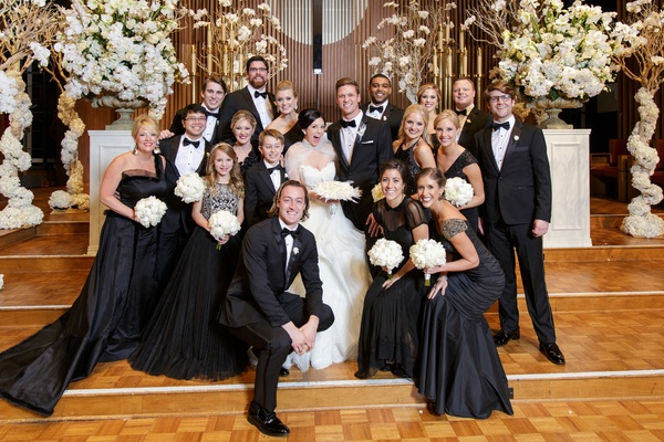 bride in lazaro ball gown, bridesmaids in mismatched black dresses, junior bridesmaid, groomsmen tux