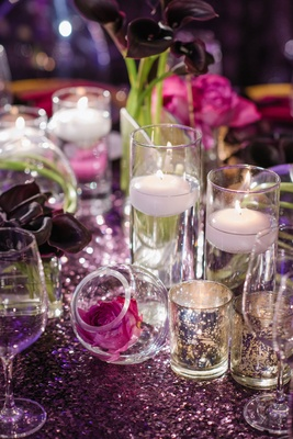 Wedding reception table with candle votives mercury glass floating candles and single flowers in orb