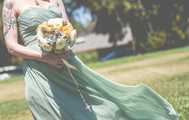 Bride holding yellow bouquet with succulents and flowers