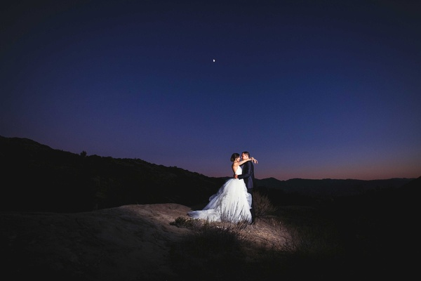 newlywed bride and groom embracing during night reception in outdoor space southern california