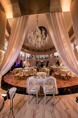 White sweetheart table with modern chairs at a reception in the Rotunda of The Westin Colonnade