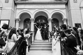 black and white photo of bride and groom leaving greek orthodox church wedding ceremony guests