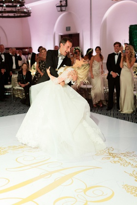 groom dipping bride during their first dance as they laugh together