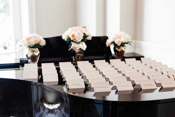 wedding reception cocktail hour white escort card on top of shiny black piano pink flowers