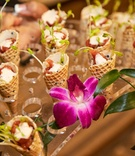 cocktail hour appetizers served in waffle cones with fresh flower accents
