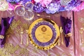 regal-themed wedding reception, shiny gold charger plate, gold menu with purple border