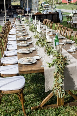 Farm wedding reception wood table with tan runner, leafy garland, candles on grassy space