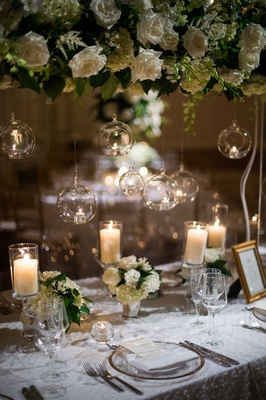long table small and tall floral arrangements white flowers foliage hanging glass balls