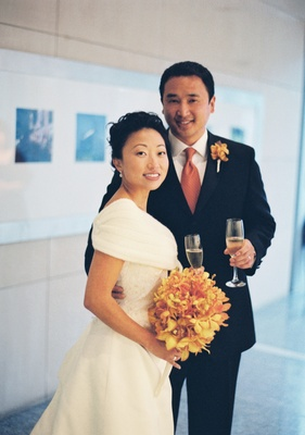 Bride in a Burberry shawl and groom in a black tuxedo with orange tie