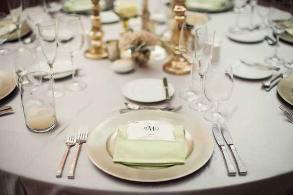 Silver tablecloth on wedding reception table with metallic charger plate light green napkin menu