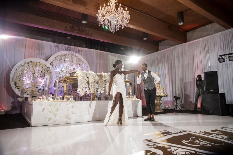 wedding reception bride in high slit dress groom in vest dance floor in front of sweetheart table