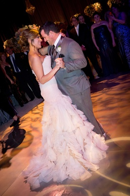 Bride in strapless Mark Zunino blush wedding dress with ruffle skirt first dance with smiling groom