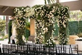 Wedding ceremony greenery white flower chuppah ceremony structure black guest chairs country club