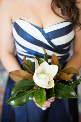 Bridesmaid in sparkly navy white stripe bodice dress with magnolia bouquet