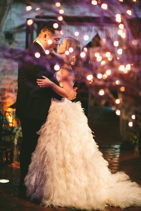 Bride in Monique Lhuillier dress with groom at reception