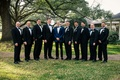 Groom in navy blue tuxedo boutonniere with groomsmen in regular black white tuxedos on grass lawn