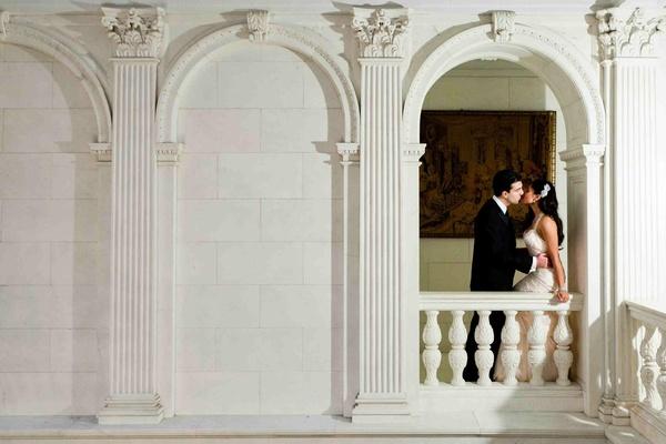 Groom kisses bride on mansion balcony