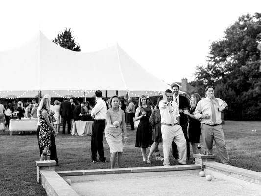 Black and white photo of guests playing bocce ball lawn game at outdoor wedding tent reception