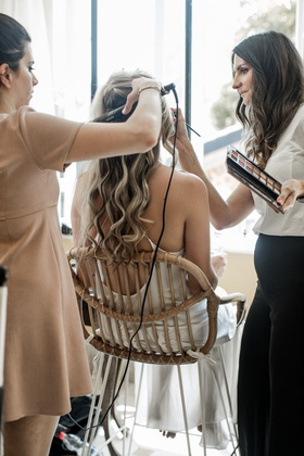 bride in pretty slip dress long curled hair getting glam with hairstylist and makeup artist