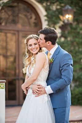 bride in mira zwiliinger wedding dress long blonde hair groom kiss on cheek blue suit yellow tie
