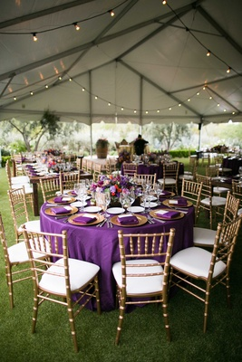 purple table linens gold charger plates colorful floral centerpieces gold chairs tented reception