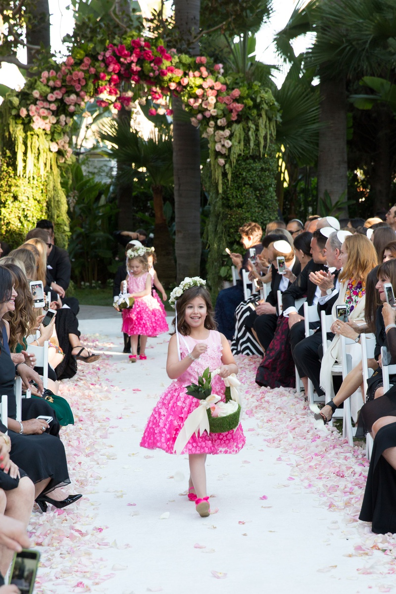 Wedding ceremony flower girls in pink dresses green baskets pink shoes walking down aisle
