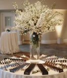 wedding reception white stock in glass vase black escort cards white tablecloth