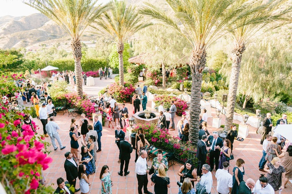 guests and family at wedding cocktail hour reception terracotta tile pink bougainvillea palm trees