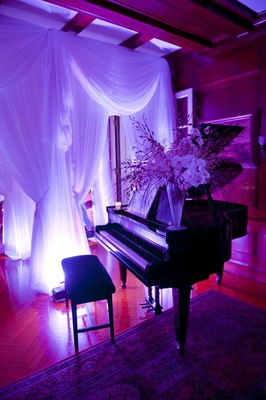 Wedding reception baby grand piano with purple lights