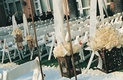 White ceremony chairs and aisle runner with white roses