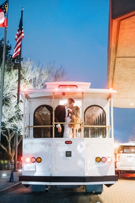 Bride in berta wedding dress long blonde hair kissing groom on back of trolley car white flags