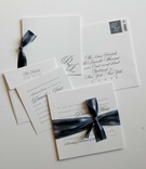 white paper invitations with blue lettering and accents in calligraphy