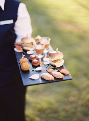 Server holding platter tray with balls, soup shooters, slider, appetizers outdoor cocktail hour