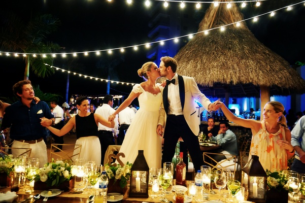 Bride and groom kiss while doing circle dance at reception